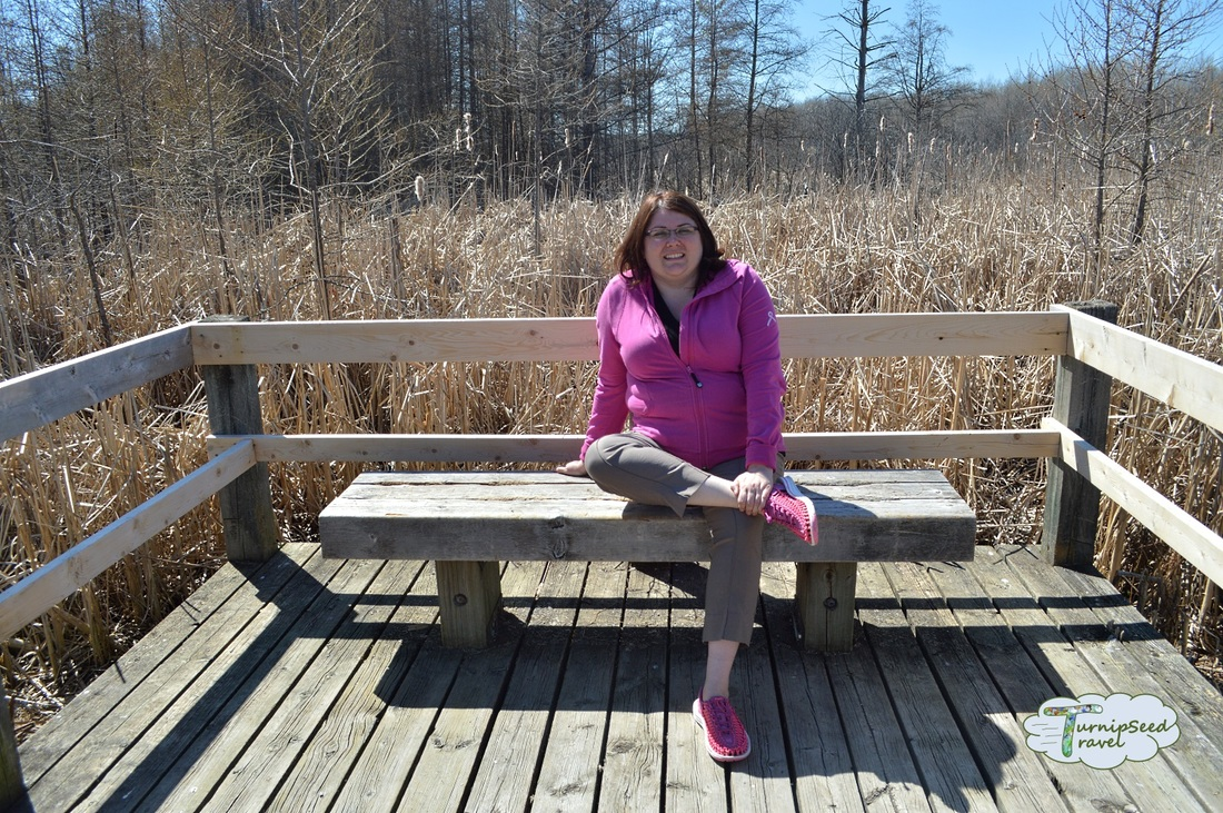 Hiking Mer Bleue Bog in Ottawa: Vanessa sits on a bench on the boardwalk