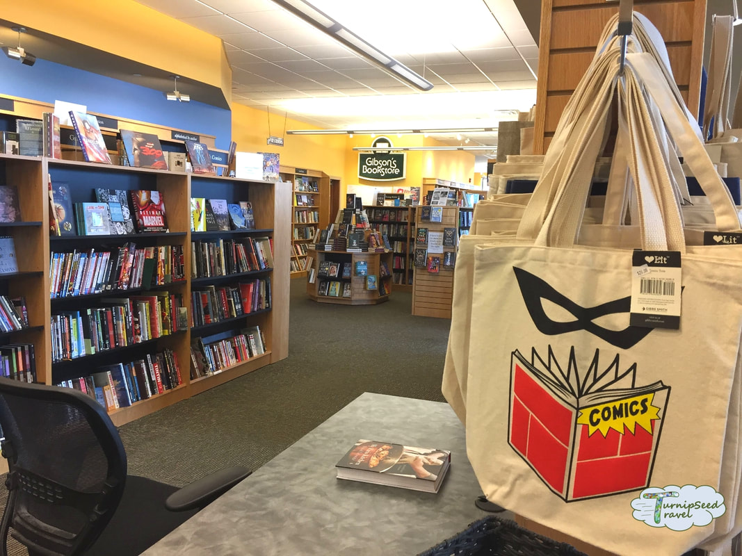 Interior of Gibson's bookstore showing shelves of books and canvas book bags on a rack Picture