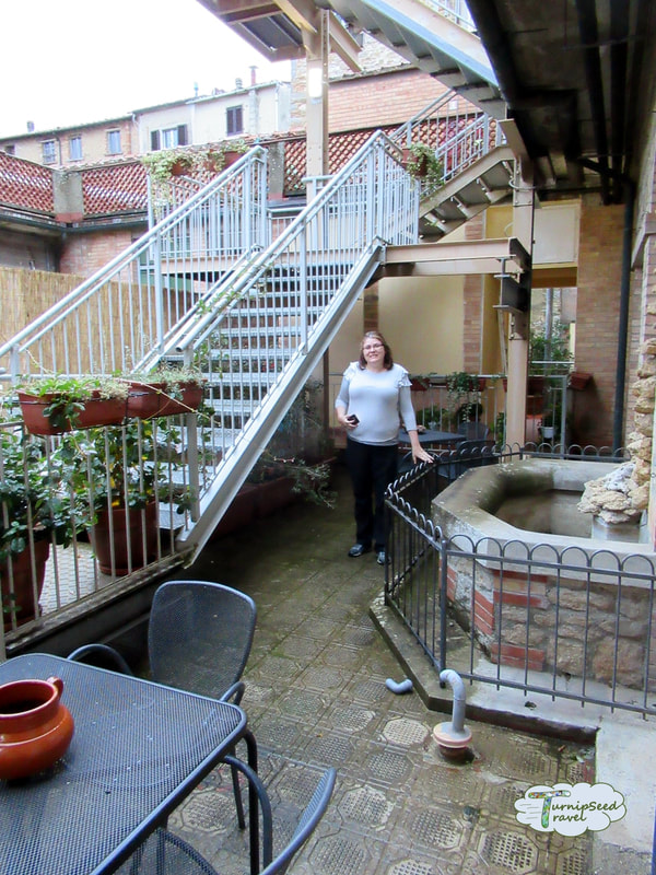 Vanessa stands in a courtyard balcony at an Italian hotel Picture