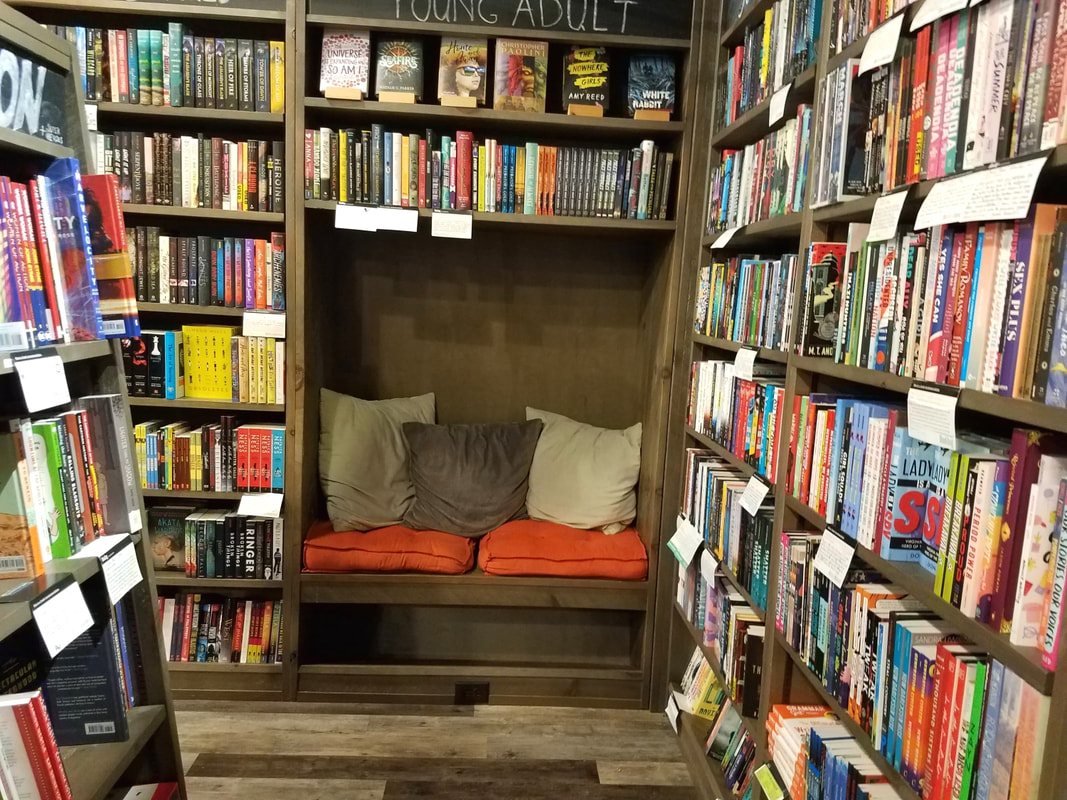 This is a bookstore & Bookbug: A padded reading nook with cushions set among the bookshelvesPicture