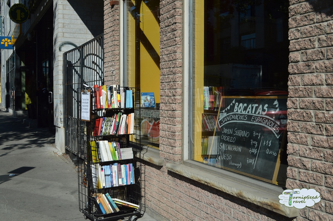 Outside the brick building of the Spanish Library, Montreal with a small rack of books outside and a menu in the windowPicture