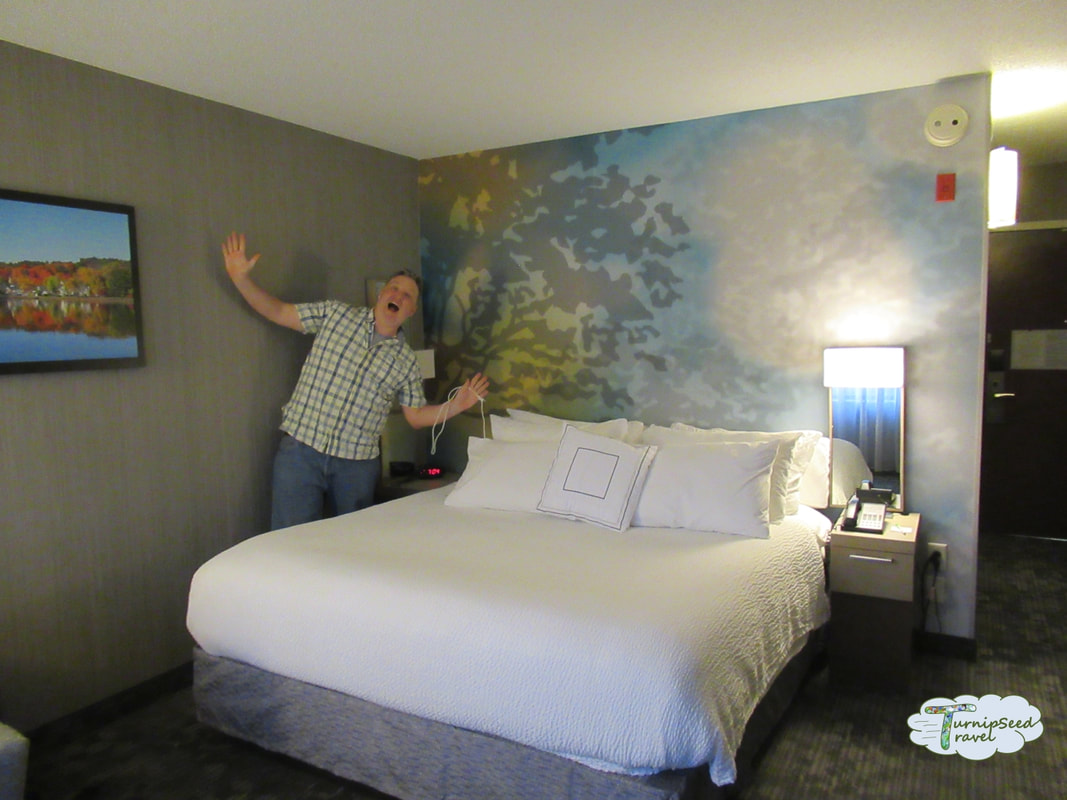 Ryan waves by a hotel bed covered in white linens