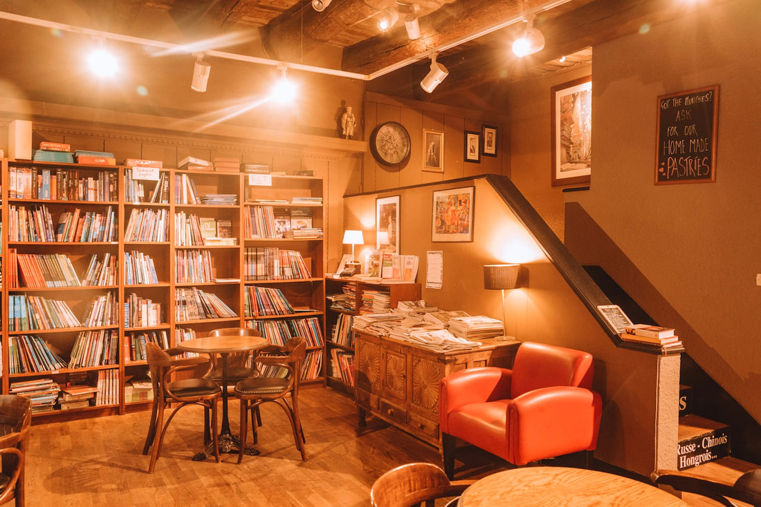 Interior of Books and Bar: Shelves of books and chairs to sit and read with art on the wallsPicture