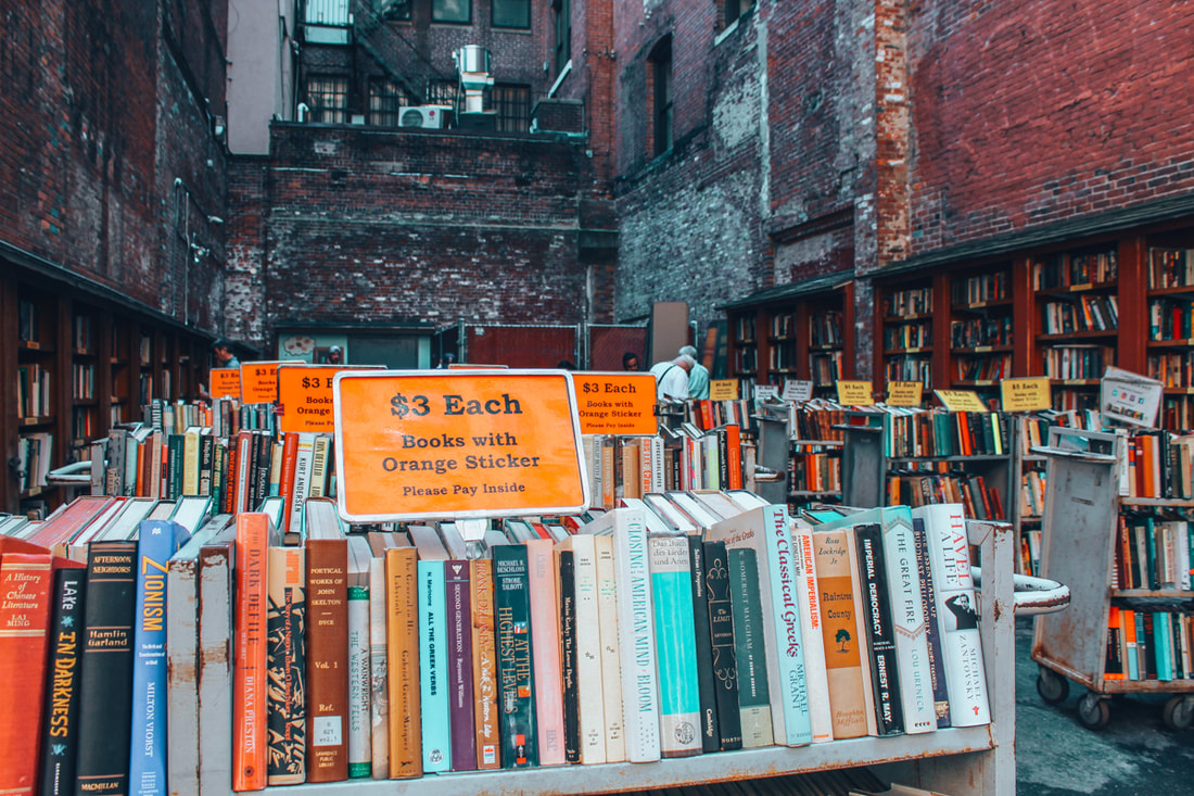 Rows of books sit outside on shelves in an alley lined with red brick buildings Picture