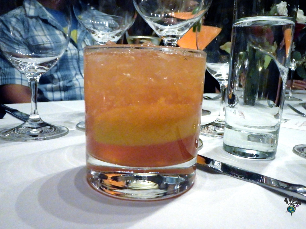 Brown-orange cocktail with lots of ice and a lemon wedge inside at Plonk Missoula Picture