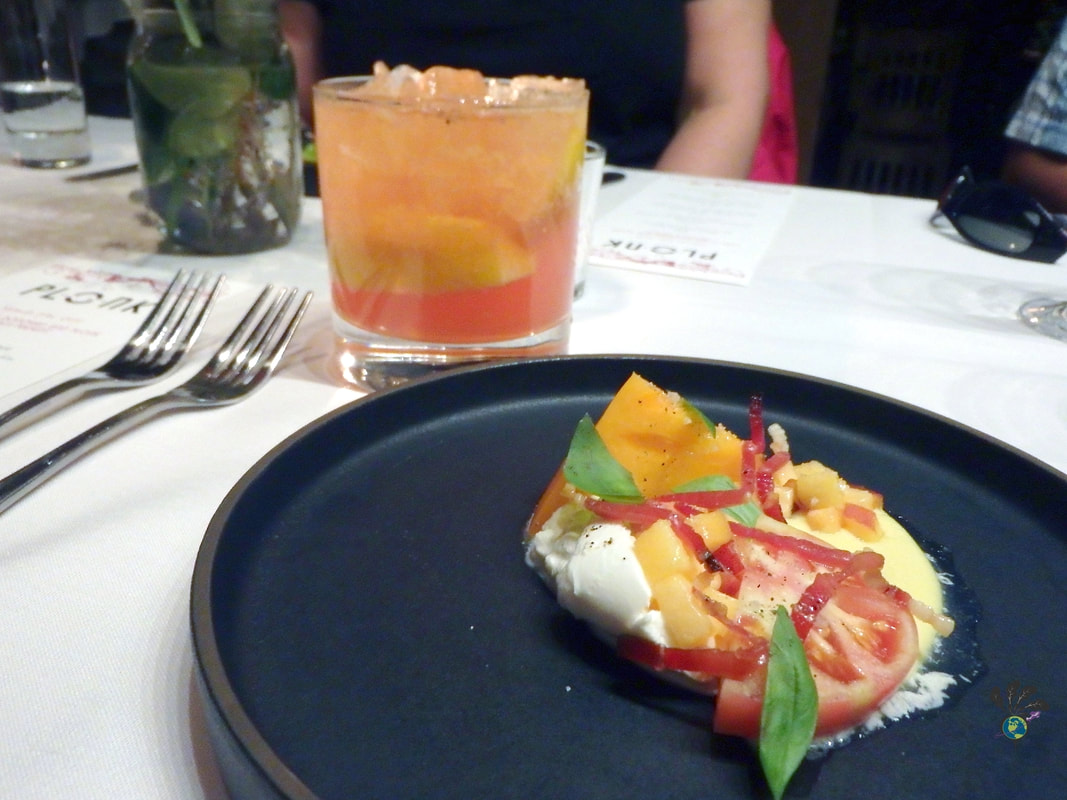 Black plate with a tomato salad with basil and peaches and cheese at Plonk Missoula Picture