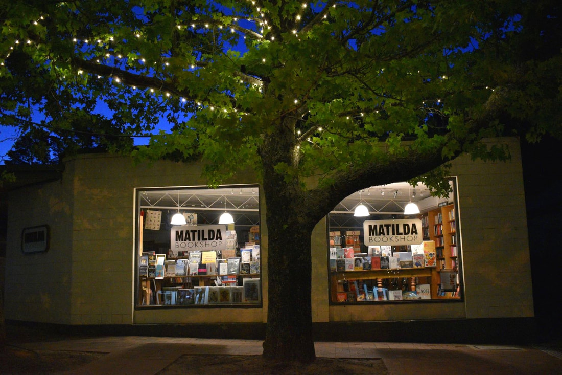 Exterior of the Matilda bookstop at night, with a leafy tree in front of the windows showing bright lights and shelves of books and decorations