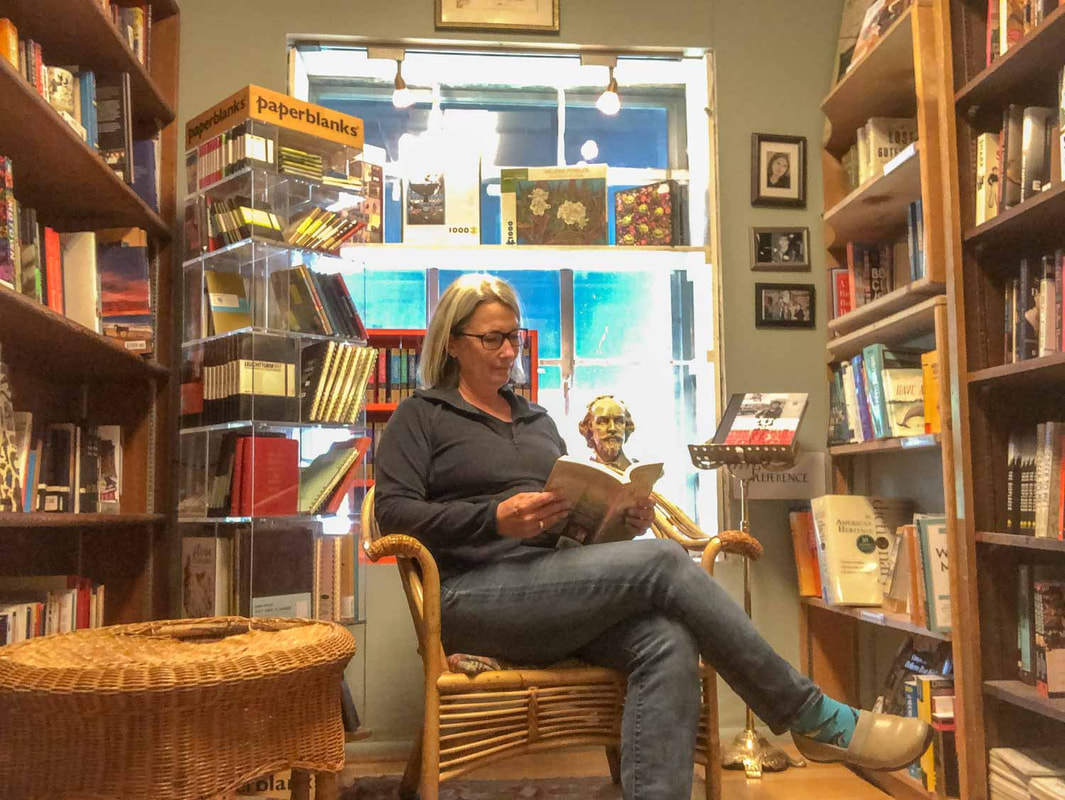 Woman sits on a chair and reads while surrounded by bookshelvesPicture