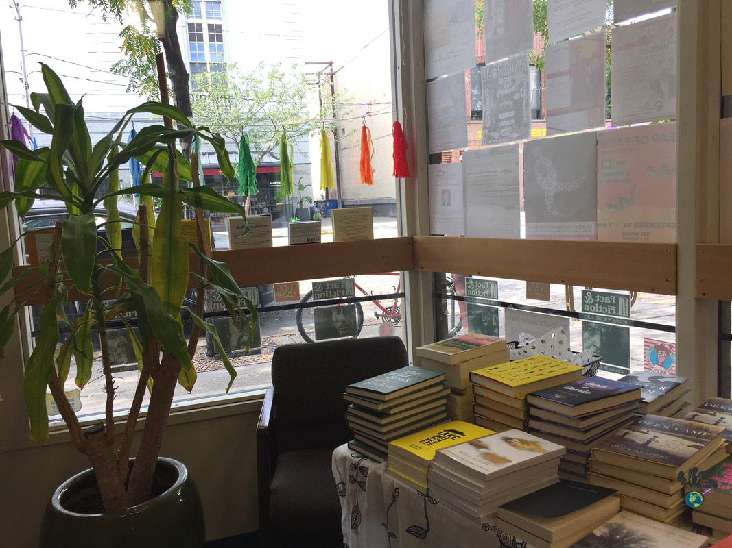 Stack of books on a table by a window adored with colorful tassels and a plant in the foreground Picture