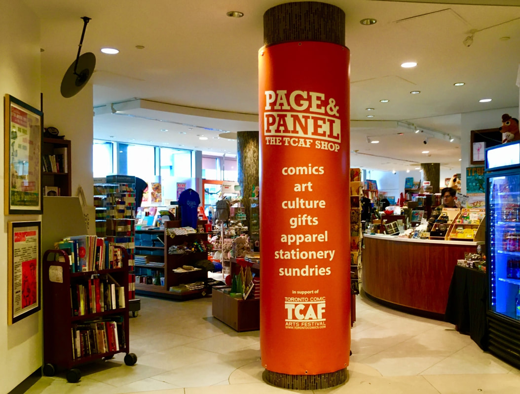 Interior of Page and Panel, with a large round pillar wrapped in orange advertising the store's services in the middle Picture