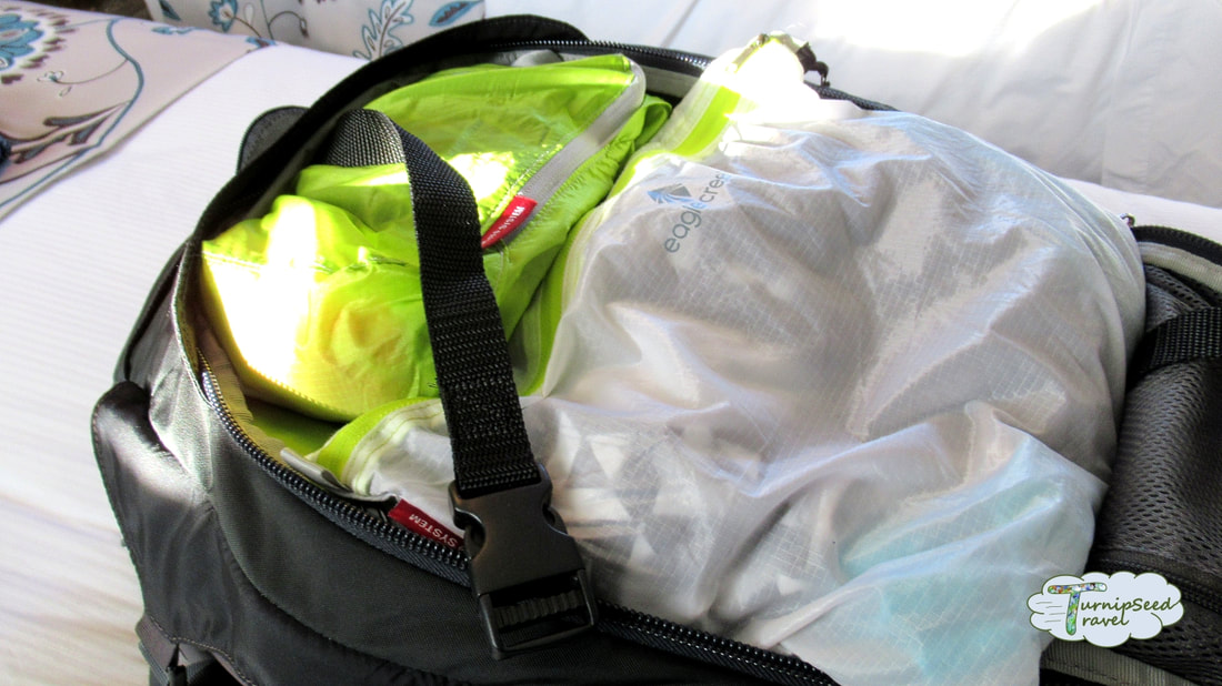 Backpack with white and green packing cubes to illustrate minimalist packing lists and traveling with paracord Picture