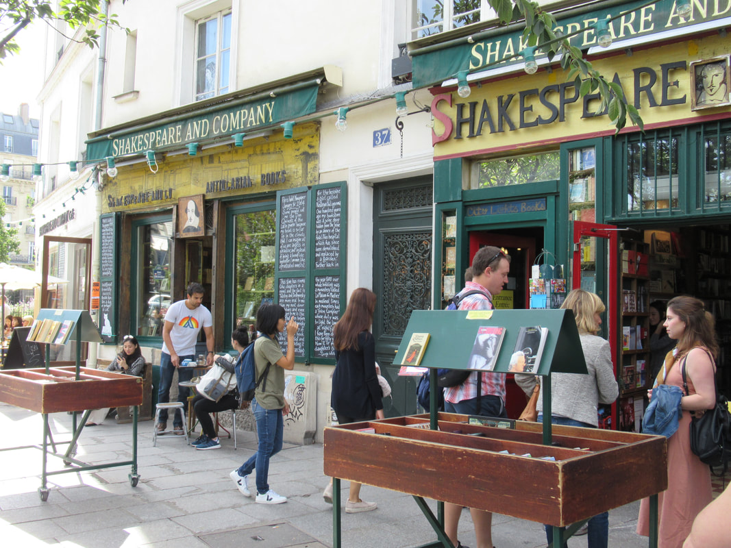 People browsing the outdoor book bins at Shakespeare and Company on a sunny day Picture
