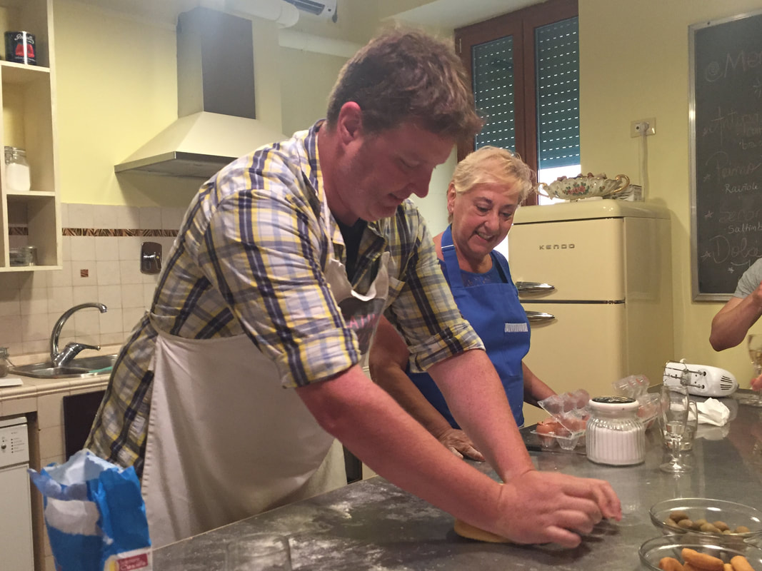 Ryan and a grandmother in Rome roll out pasta dough on a stainless steel table.