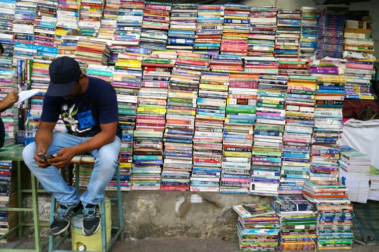 a book seller in India sits on a stool in front a several really high stacks of booksPicture
