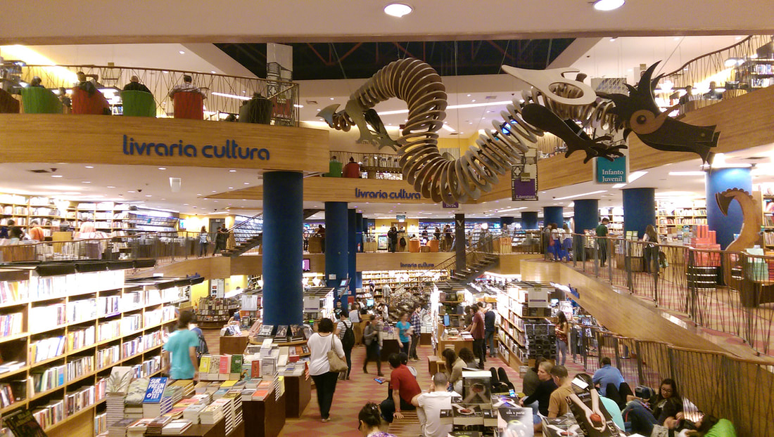 Interior Livraria Cultura from balcony with shelves of books, people shopping, and a large dragon puzzle suspended from the ceiling