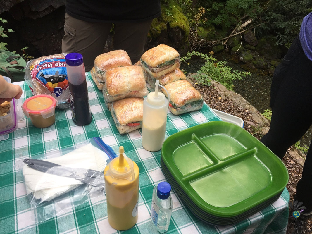 Camping table set up with sandwiches and condiments