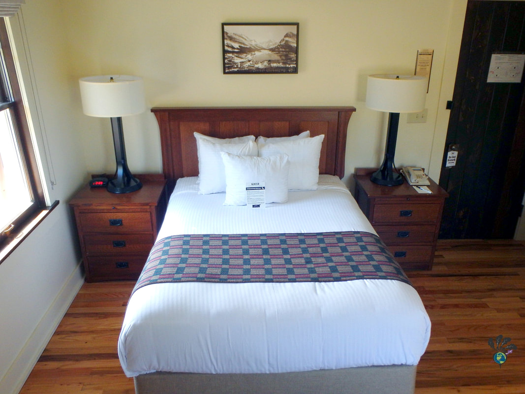 Interior bedroom shot with a queen size bed flanked by two night stands at Many Glacier Hotel Montana Picture