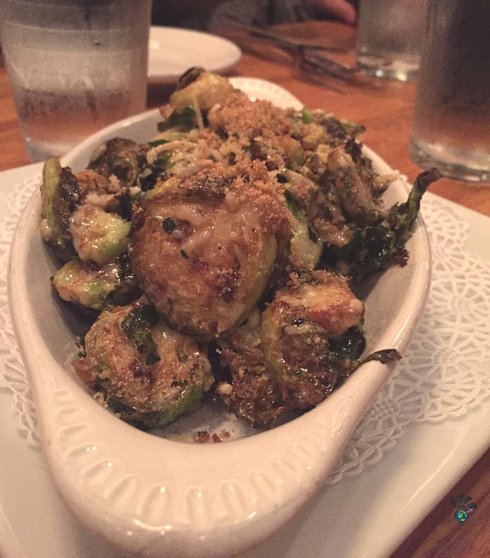 An oblong white dish of roasted Brussels sprouts with crusted cheese and bread crumbs on top at the Tupelo Grille in Whitefish Montana Picture