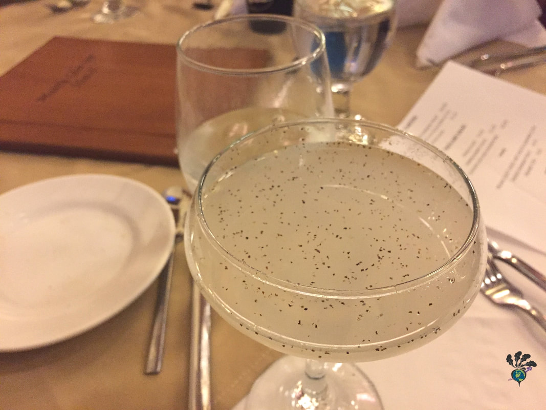 Old fashioned champagne flute filled with a cocktail speckled with black pepper. Whistling Andy Distillery and the Many Glacier Hotel's Ptarmigan Dining RoomPicture