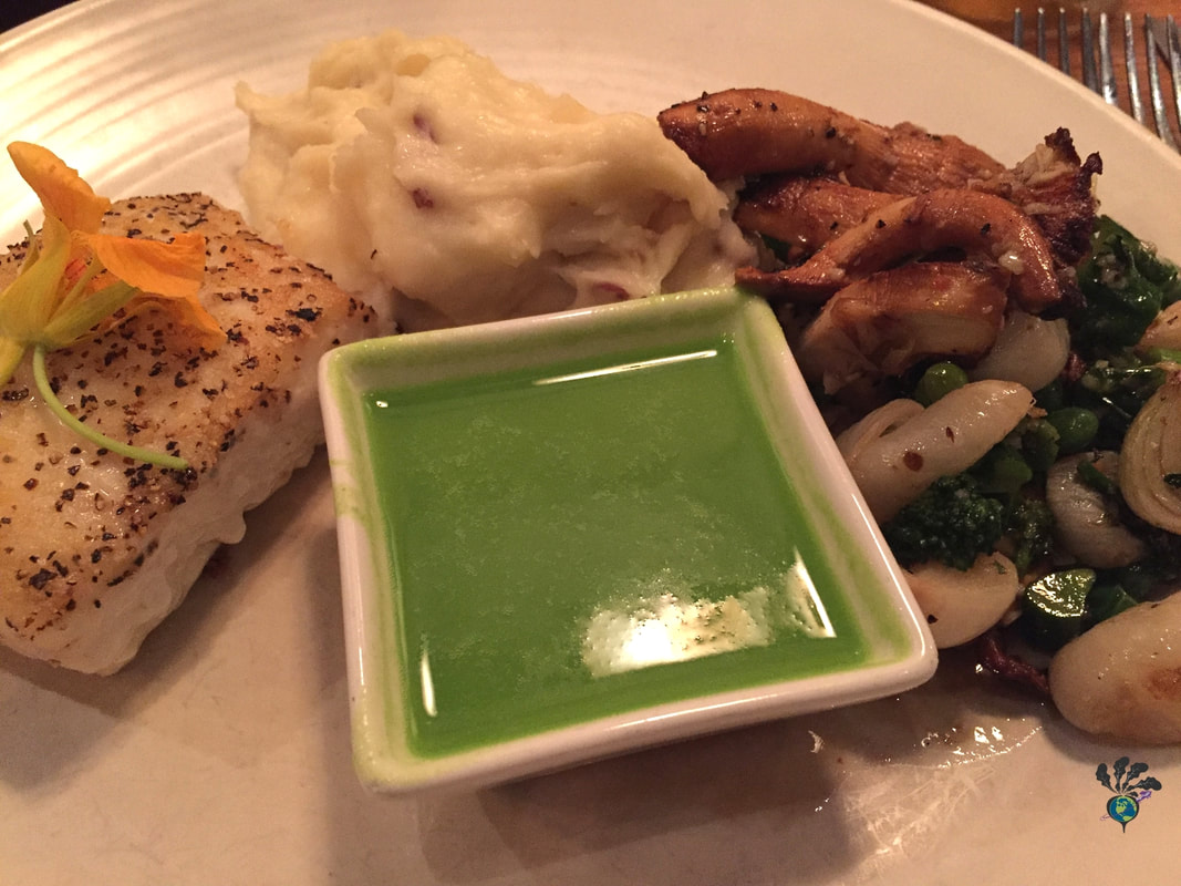 A plate showing baked halibut, mashed potatoes, mushrooms, green vegetables, and a bowl of bright green asparagus puree at Tupelo Grille in Whitefish Montana Picture
