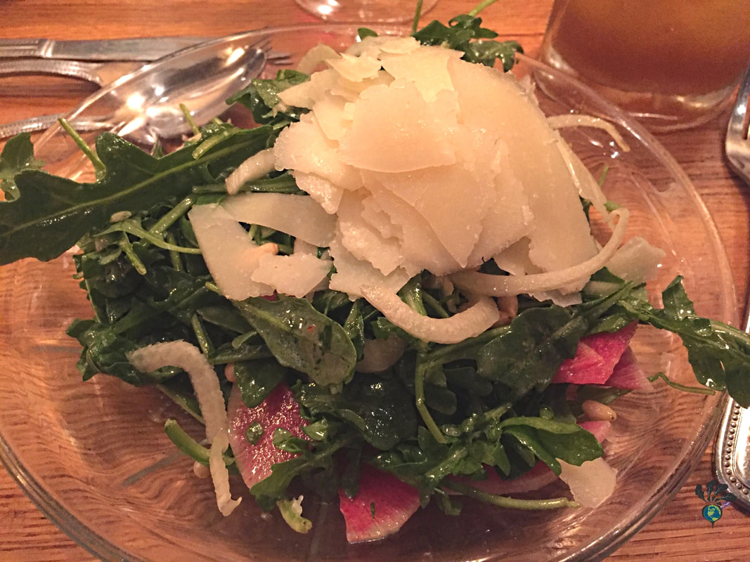 Arugula salad on a glass plate with pecorino cheese on top at Tupelo Grille WhitefishPicture