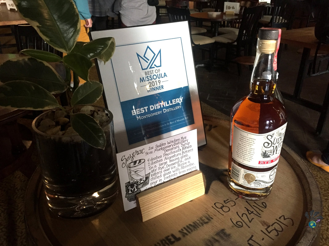 Bottle of whiskey and an award plaque sit on top of a whiskey barrel at Montgomery Distillery in Missoula MontanaPicture