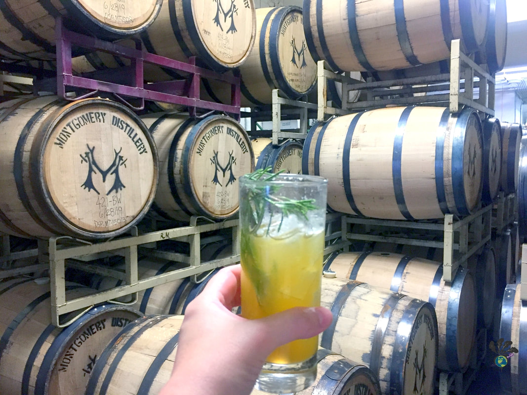 Made in Montana: Visiting a Montana Distillery to see stacks of barrels, with highball cocktail glass in my hand.Picture