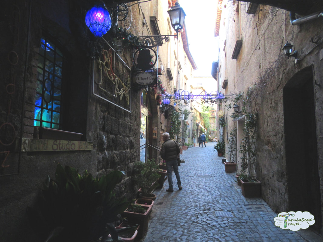 Shops down a cobblestone alley in Orvieto by TurnipseedTravel