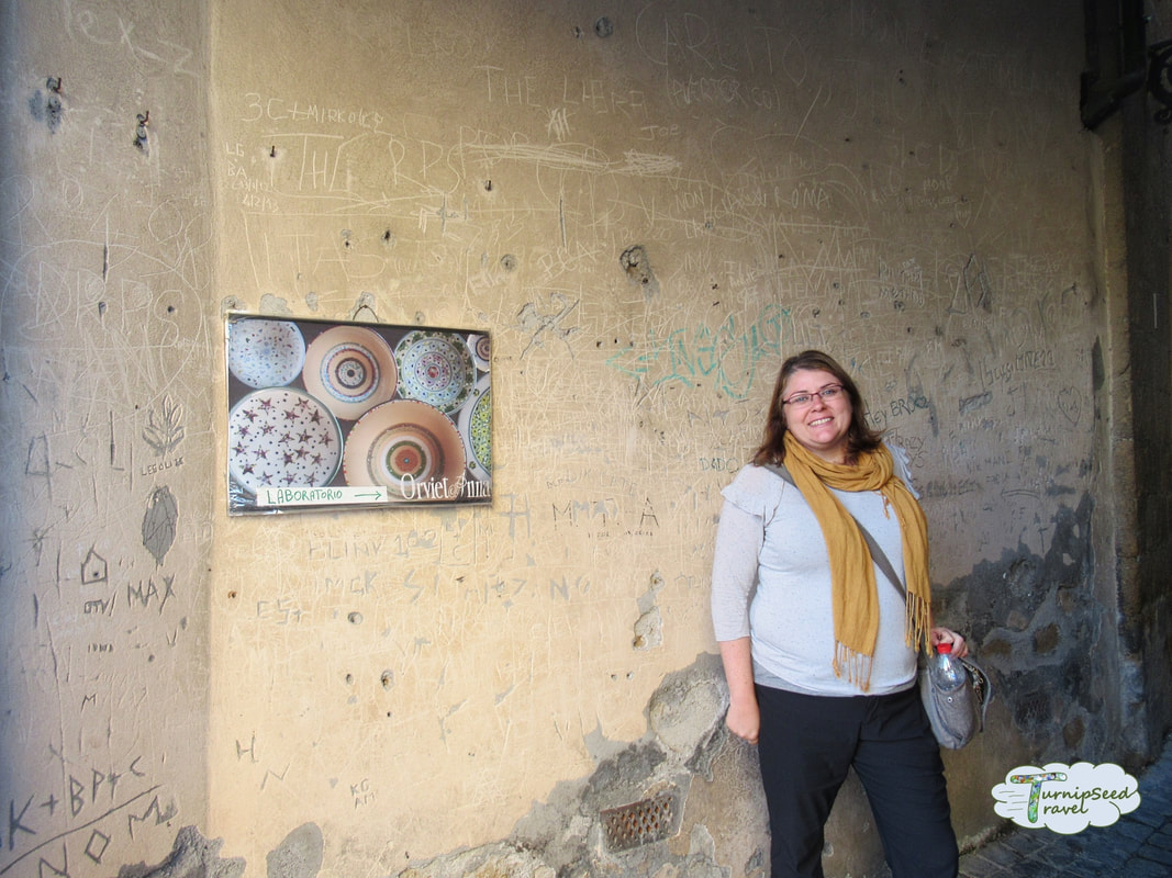 Posing next to a pottery shop sign in Orvieto by TurnipseedTravel
