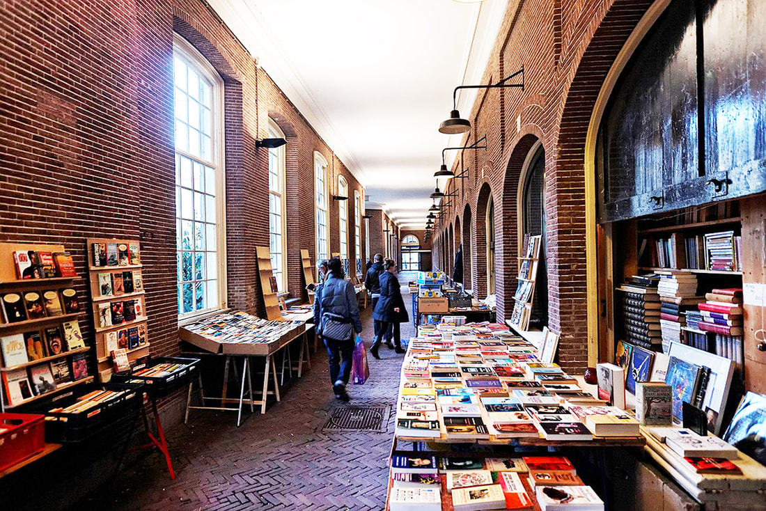 interior courtyard of a bookstore with multiple rounded arches and red brick walls Picture