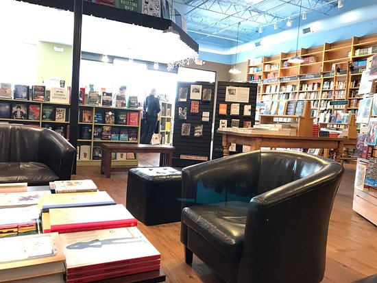Black leather chair and coffee table surrounded by bookshelves Picture