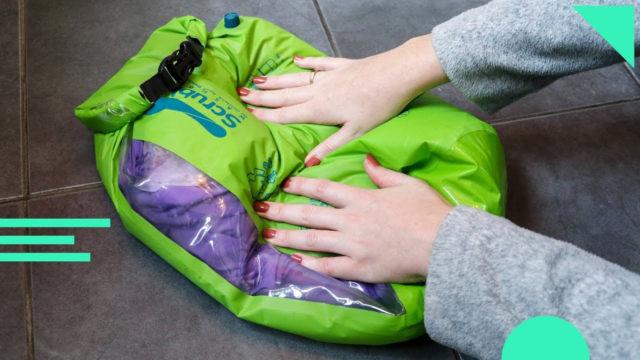 Scrubba Wash Bag review with a bright green wash bag being used by someone wearing a grey sweater