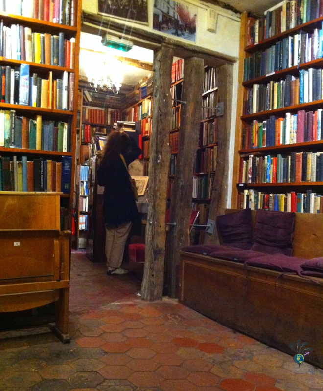 Interior of Shakespeare and Company, showing a woman browsing high bookshelves on a floor of hexagon tilesPicture