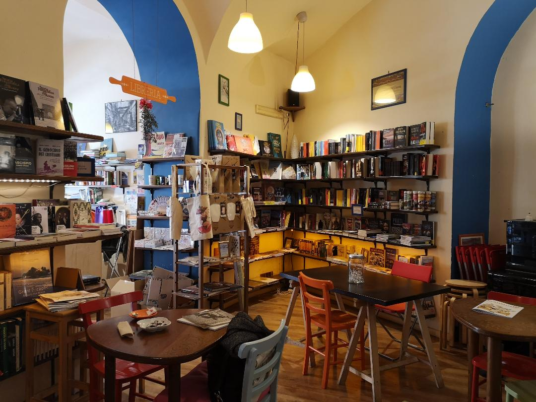 Bookstore interior with white walls and blue arches, small tables, and bookshelves