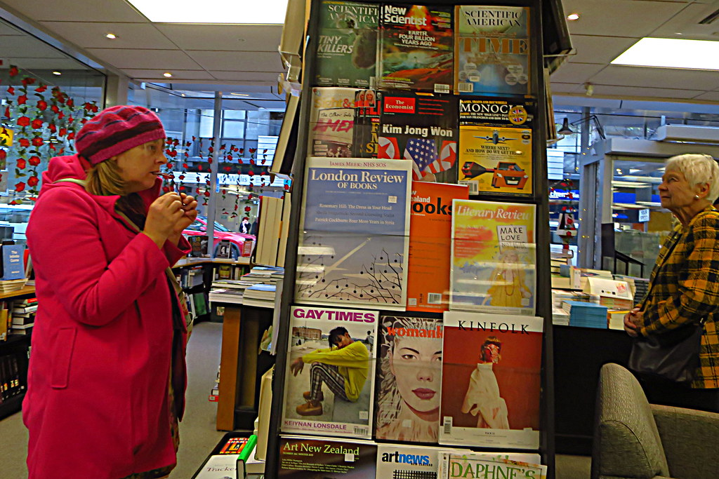 Two women stand on either side of a large colorful magazine rack to look at the selectionPicture
