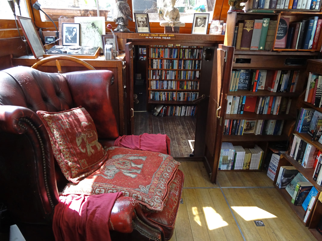 Interior of Word On The Water - a red leather arm chair in a corner surrounded by book shelves Picture
